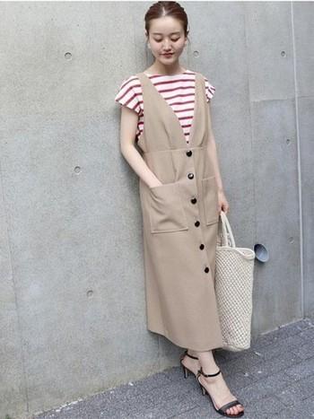 鮮やかなレッドのボーダーは、ベージュのジャンパースカートを合わせることで優しい雰囲気に。ボートネックがデコルテラインをきれいに見せてくれ、女性らしさを引き立てます。足元をスニーカーに変えてカジュアル感をプラスしても素敵です。