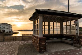"""夕暮れ時の鐙摺バス停。 向こうに見える白い建物は""""フランス風創作海辺料理""""を提供してくれる「葉山 日影茶屋 の系列店「LA MARÉE (レストラン ラ・マーレ)」)。"""