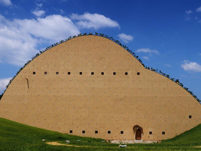建築史家、建築家である藤森照信氏が設計した、すり鉢状の緑の斜面に立つ土の建物。思わず足を止めて見入ってしまうこの不思議な建物は、多治見市笠原町にある「多治見市モザイクタイルミュージアム」という、タイルについての情報が何でも揃い、タイルの新たな可能性を生み出すミュージアムなんです。