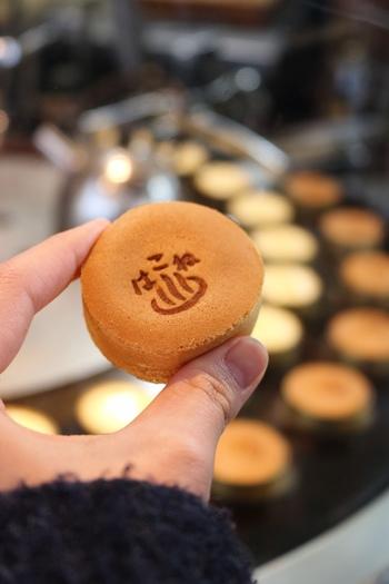 """箱根湯本駅前には、思わず引き寄せられるカシャカシャとお饅頭を焼く軽快な音と甘い香りが漂います。 「菊川商店」の白あんをふわふわの生地に包んだミニサイズの名物「箱根まんじゅう」は、食べ歩きにも最適です。  """"はこね""""という文字と温泉マークの焼き印が、レトロで可愛らしい♪"""