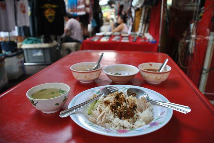 鶏にタレをかけ、スプーンとフォークで肉をひと口大にカットし、ご飯と混ぜて食べます。ご飯と肉をバランスよくミックスして口に運ぶのがポイント。