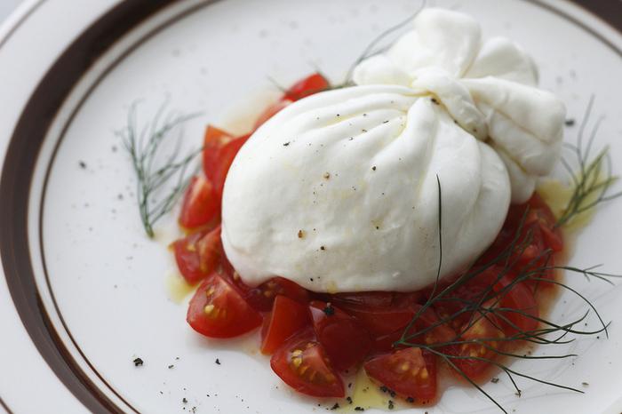 なんだか可愛らしい巾着型の真っ白なチーズ、「ブッラータ(burrata)」。イタリア南部の名産で、モッツァレラチーズと同じ製法で作られているため、見た目の質感がよく似ています。モッツァレラと違うのは、袋状の構造になっていて、中にはたっぷりのミルクと細切りチーズが詰まっていること。また外側の巾着も、袋の薄い部分とひだや結び目の厚い部分ではそれぞれ違う食感を味わえます。
