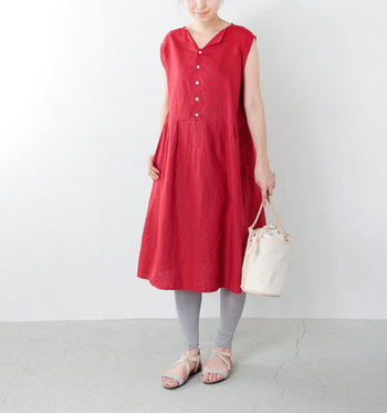 印象的な赤のワンピースに、グレーのレギンスとサンダルを合わせたスタイリングです。赤ワンピースを素足やストッキングで履くと子どもっぽくなってしまいがちですが、レギンスを合わせることで程よく大人感を演出できます。