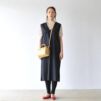 ちょっぴり変わったデザインのワンピースに、黒のレギンスと赤パンプスを合わせた着こなし。シューズと色を合わせたボーダートップスも、ネイビーのワンピースと好相性です。