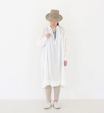 白のシャツワンピースに、ベージュのサルエルパンツをレギンス風に合わせたコーディネートです。透け感のある白シャツから覗く、ボーダーのインナーが良いアクセントになっています。デニムパンツなどを合わせるよりも、レギンスの方が涼しげな印象がありますね。