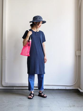 ネイビーのTシャツワンピースに、デニムパンツを合わせたワントーンコーデ。ハットもネイビーで合わせて、季節感のあるピンク色のバッグを指し色として活用しています。ちょっとしたアウトドアにもOKの、カジュアルコーデです。