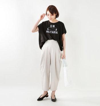 白のワイドパンツに、黒のロゴTシャツをタックインしたスタイリングです。ドルマンスリーブのゆったりシルエットが印象的なトップスは、前だけを入れるフロントタックインで好バランスな着こなしに。