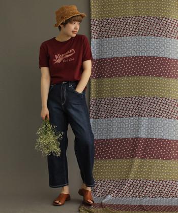 ボルドーカラ―のロゴTシャツは、ストレートタイプのデニムと合わせるだけで、シンプルなのにこなれ感のある着こなしに仕上がります。茶色の帽子とサンダルで、さらに大人っぽさをアピールできるスタイリングに。