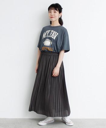 古着感のあるTシャツに、アメリカンなフットボールロゴをプリントしたアイテム。チャコールグレーに合わせたダークトーンのプリーツスカートで、ロゴTシャツをシックな印象に着こなしています。