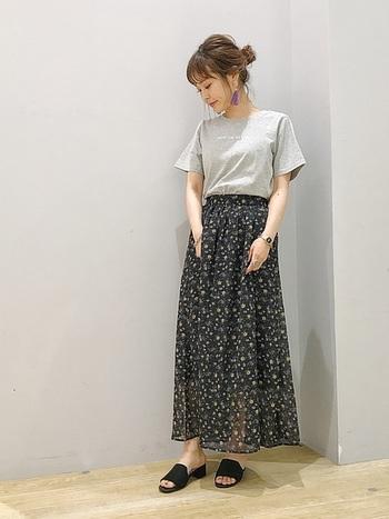 白文字のさりげない英字ロゴが程よい大人感を演出してくれるグレーのTシャツ。黒の花柄スカートを合わせて、華やかさをしっかり演出できるコーディネートに。