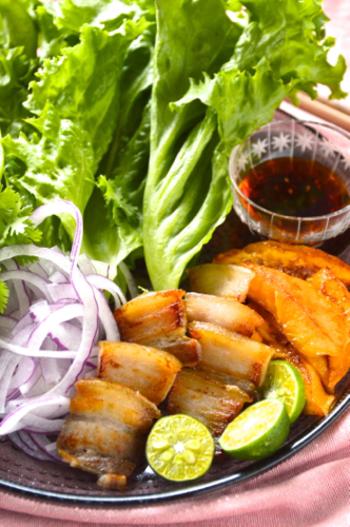 """沖縄の豚の塩漬け""""スーチカー""""や焼きマンゴーなどを葉っぱでくるみ、シークワーサーを搾ります。あとは、石垣島のラー油を付けて召し上がれ。コクがあるのに爽やかで、沖縄と韓国のコラボレーションが楽しめます。"""