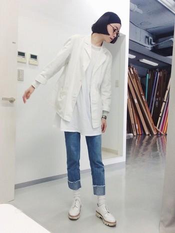 トップスと足元を白のワントーンでまとめ、ダメージ加工が施された淡色デニムを合わせたスタイリング。裾を幅広にロールアップすることで、足元に視覚的にグラデーションを作り、コーデ全体と爽やかに馴染ませています。