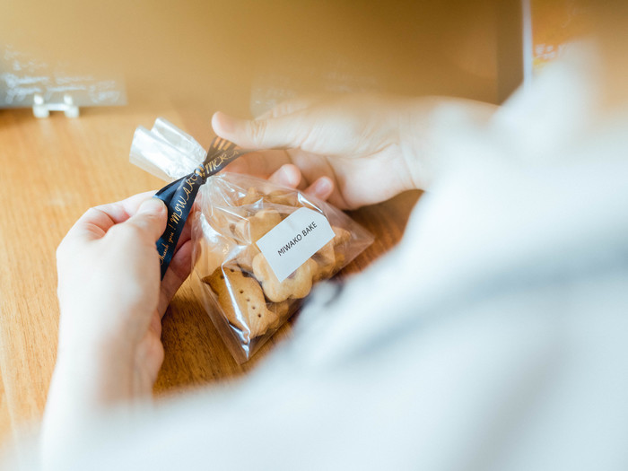 店名を印字したリボンテープ。特別なプレゼントであれば日付や、贈り先の名前を入れても良い…とアイディアは広がります。 【テープ情報】文字色:金 テープ色:ネイビーブルー(リボンテープ) テープ幅:12mm