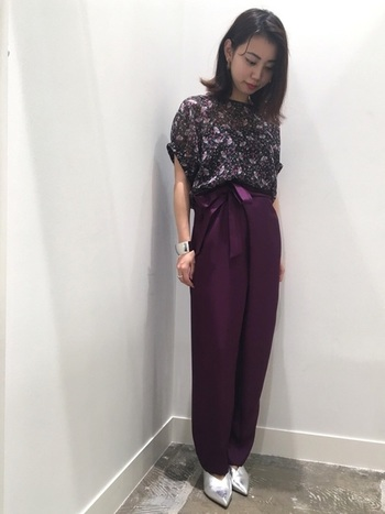 花柄トップスとパンツを赤紫のワントーンでまとめたシックなスタイリング。太めのバングルとパンプスのシルバー輝きが、シャープなアクセントを効果的に加えています。