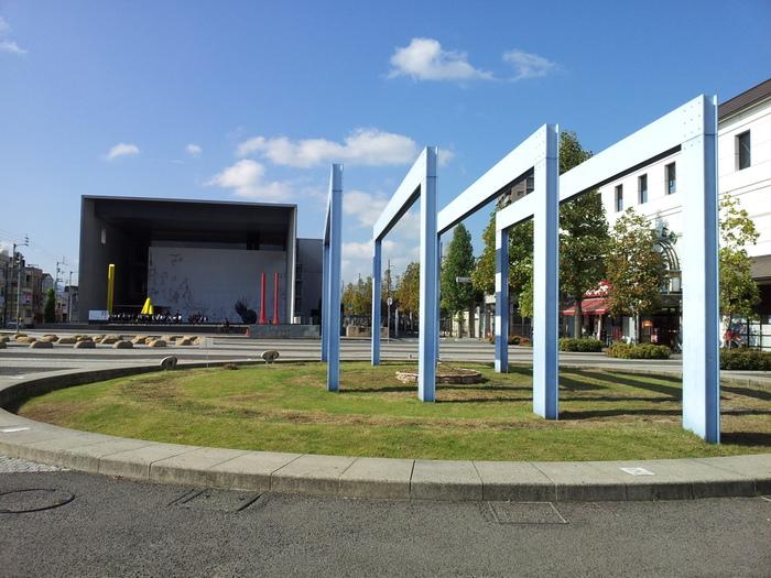 香川県丸亀市にあるこの美術館は、全国でも珍しい「駅前美術館」です。写真の右手に見える白い建物が、JR丸亀駅。左手の、箱を横に倒したような中に黄色と赤のオブジェが見えるのが、「丸亀市猪熊弦一郎現代美術館」。本当に駅の目の前なのです。