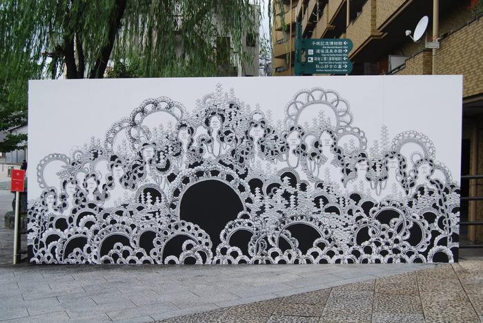 こちらは新進気鋭の画家・石井七歩さんの作品「融合しよう Let's Fusion」。街角に突然現れる大きな壁画です。温泉の湯けむりの中に溶け込み、風景と自己が消失していく感覚を表現しているのだとか。