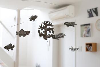 """■鹿児島睦 """"ZUAN"""" Mobile(モビール)AKVAARIO 水族館って大人になるとあまり行かなくなるけれど、久しぶりに訪れると単純に感動してしまうもの。ひらひら泳ぐ魚たちの光景を、お部屋で再現してみませんか。 ふわふわと空間を泳ぐ、何とも涼し気な魚のモビールは、光が当たるとキラキラと反射した銀色の模様が壁に映し出されて、まるで本当に海の中を泳いでいるよう。"""