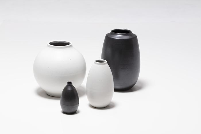 2018年の新作「OUUR TONE VASE」。約400年の歴史と実績をもち、江戸時代には幕府へ壺を献上していたという「信楽焼き・明山窯」とのコラボレーションで誕生した花器です。  現代のインテリアにも合わせやすい白と黒のモノトーンカラーが印象的ですが、注目したいのはネイサン・ウィリアムスが最もこだわったフォルムと質感。そのひとつが釉薬ののせ方で、一般的な信楽焼きの風合いとは異なるマットな仕上がりが魅力的です。伝統ある日本の窯元とヨーロッパのセンスが混ざりあい、和にも洋にもしっくり馴染みます。  【OUUR TONE VASE】2,052円~4,536円(税込)