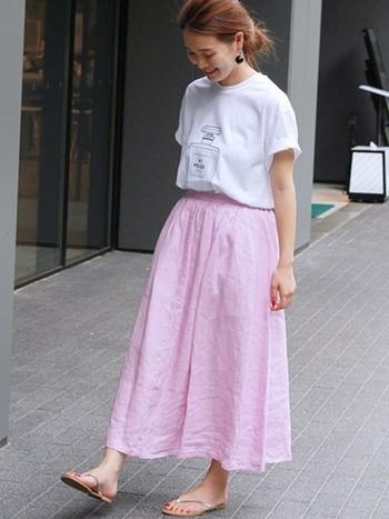 シャネルの香水瓶を思わせるポップなイラストTシャツ。ピンクのフレアスカートでかわいらしくナチュラルにまとめて。女性らしく軽やかな雰囲気が素敵です。