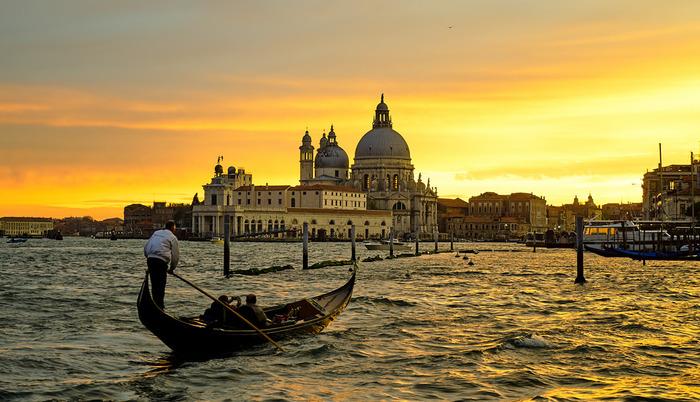 """""""イタリアでバカンスを過ごす""""といえば、ビーチリゾートをイメージする方が多いのではないでしょうか。 しかし海近くのリゾート地でも、全く異なる雰囲気を楽しめるのが、水の都「ベネチア(ヴェネチア)」。""""ベネチアンマスク""""や""""ベネチアングラス""""で、その名に聞き覚えのある方も多いでしょう。  世界遺産に登録されているその街並みは、海や空、陽の光と融合して、独特の雰囲気を放つ絶景に。サンセットタイムは、また格別です。"""