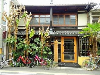 地下鉄東西線「京都市役所前駅」から歩いて約6分のところにある『Cafe Bibliotic Hello!(カフェ ビブリオティック ハロー!)』は、築150年の町屋をリノベーションして作られたブックカフェです。店前に立つバナナの木が目印です。