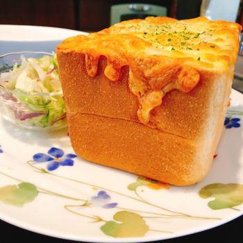 """運ばれてきて驚くのが、そのボリューム。なんと、パンの厚さは13cm、総重量は約600gもあります。器になっているパンは、宮ノ下の有名店「渡邊ベーカリー」の食パンを使用。パンからあふれるほどたっぷり入ったシーフードグラタンの香に、食欲をそそられますね。店名通り""""ぱんのみみ""""までおいしくいただける、シェアしても十分なボリュームです。"""