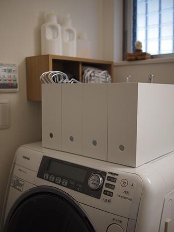 洗濯機の上に「ファイルボックス」を4つ並べて、ハンガーやピンチなどの洗濯グッズの収納に。絡まりやすいピンチハンガーもノンストレスで取り出せます。