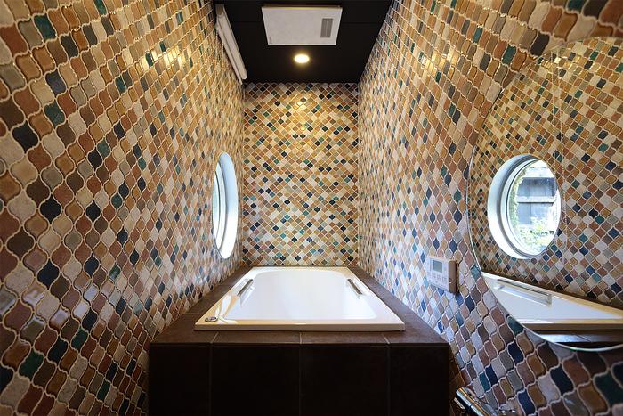 浴室はカラフルなタイル貼り。丸い窓から庭の景色を眺めながら、旅の疲れをゆっくりと癒すことができます。