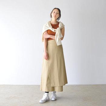 リブデザインが大人な雰囲気のノースリーブに、変形シルエットのベージュスカートを合わせたスタイリング。方から羽織ったカーディガンは、暑い日には日避けにしたり、腰に巻くのも◎