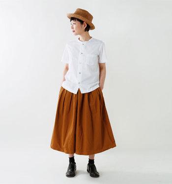 スカートのようにふわっと広がるブラウンのワイドパンツに、白の半袖シャツを合わせたコーディネート。足元は黒でまとめて、白シャツの上品さをしっかり引き締めるアクセントカラーとして活用しています。ハットが旬を感じさせる、大人の爽やかコーデの完成です。