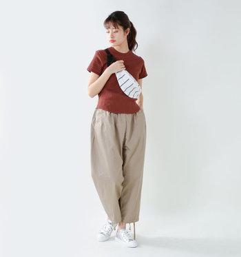 シンプルなブラウンのTシャツに、ベージュのワイドパンツを合わせたコーディネートです。トップスがタイトなアイテムなので、ボトムスにゆとりのあるものを合わせ、好バランスな着こなしに仕上げています。バッグとスニーカーで白を加えているのも、爽やか見えするポイントになっていますね。