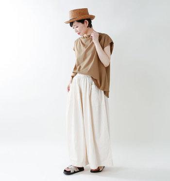 ゆったり着られるベージュのプルオーバーに、白のワイドパンツを合わせたスタイリング。サンダルやハットで季節感をプラスし、涼し気で爽やかなベージュコーデに仕上げています。