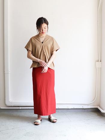 ベージュの半袖トップスに、赤のタイトスカートを合わせたコーディネートです。ベージュはどんな色にも馴染みやすいので、何を合わせたらいいのか迷ってしまうような印象的なアイテムにも、合わせやすいのが魅力ですね。