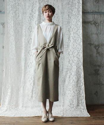 ベージュのジャンパースカートに、透け感のある白ブラウスを合わせたコーディネート。デザイン性の高いベージュワンピースのインナーに、女性らしいブラウスを合わせるだけで上品な着こなしが完成します。レイヤードが苦手な方でも、着こなしやすい組み合わせですね。