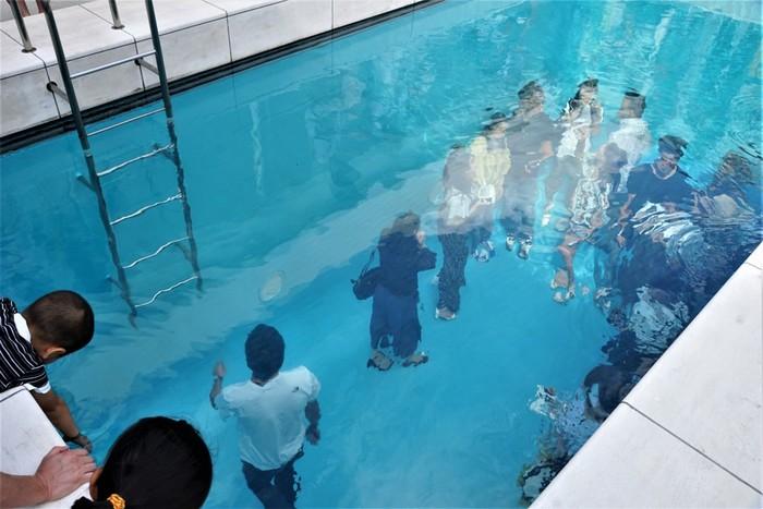 こちらはアルゼンチンの現代アーティスト、レアンドロ・エルリッヒ作の「スイミング・プール」。一見ごく普通のプールに見えますが、上から覗き込むと、プールの中にいる人は洋服を着たまま歩いています。その不思議な光景に驚かされますが、実際には10㎝の水を張ったガラスで仕切られているだけで、ガラス板の下は空洞になっています。プールの上からも内部からも楽しめる本作品は、金沢21世紀美術館の中でもフォトジェニックな作品として人気を集めています。