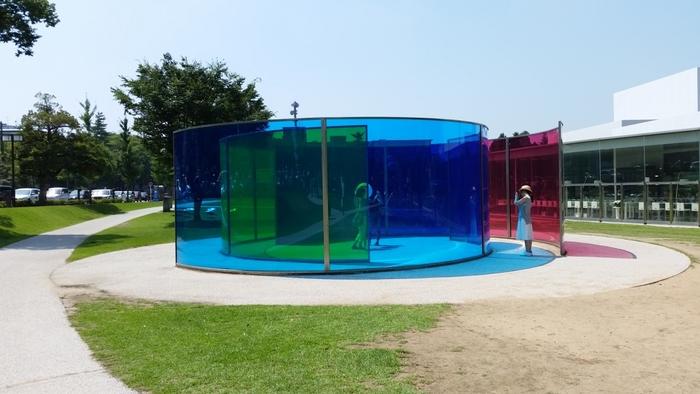 こちらはデンマークの現代アート作家、オラファー・エリアソン作の「カラー・アクティヴィティ・ハウス」。色の三原色であるシアン・マゼンダ・イエローで彩色した色ガラスの壁を、渦巻き状に配置してパビリオンを形成したユニークな作品です。色ガラスを通して見える風景や人の動き、ガラスとガラスの重なりから生まれる様々な色など。見る場所や光の角度によって色が変わり、その色を通して、いつもとは違った景色を楽しむことができる作品です。