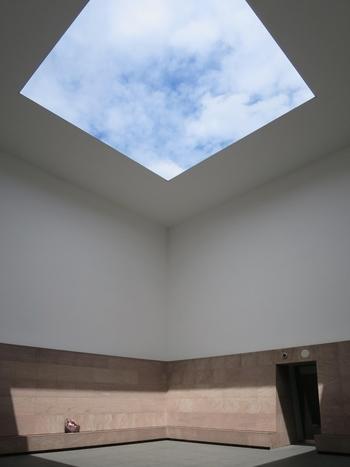 """天井の中央部分にある吹き抜けから、""""正方形に切り取られた空""""を鑑賞する「ブルー・プラネット・スカイ」。こちらはアメリカ出身の現代アート作家、ジェームズ・タレルの作品です。一日の中で刻々と変化する""""光""""をテーマにした本作品は、見る人の知覚そのものに働きかけ、日常とは異なる感覚を与えてくれます。"""