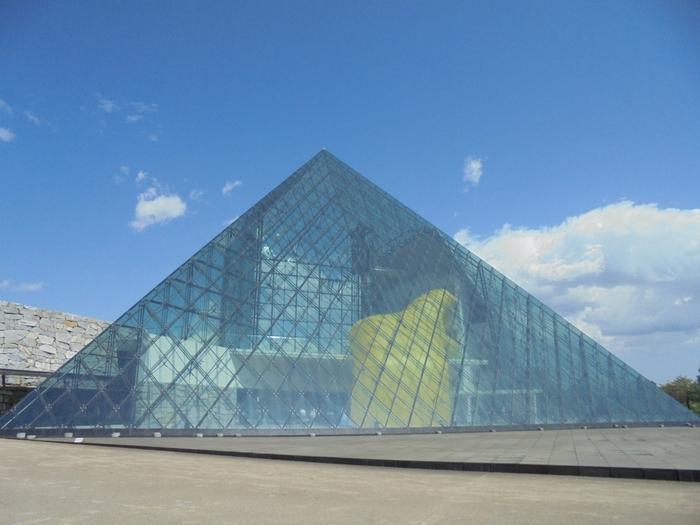 """こちらはモエレ沼公園の文化活動の拠点となる施設、「ガラスのピラミッド """"HIDAMARI""""」です。三角面・四角錐・立方体を組み合わせた美しいガラスの建物には、レストランやギャラリーなどが入っており、週末にはコンサートや美術展が開催されます。"""
