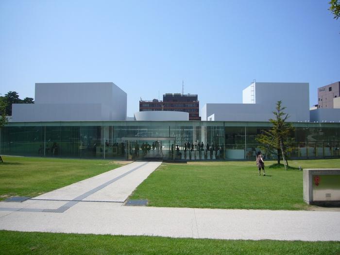 """石川県金沢市の中心に位置し、「まるびぃ」の愛称でも親しまれている『金沢21世紀美術館』。金沢の芸術・文化発信の拠点として開設され、全国から多くの来場者が訪れる現代美術館です。""""まちに開かれた公園のような美術館""""をコンセプトにした円形の建物は、訪れた人がどこからでも入れるよう、東西南北の4方向に出入口が設けられています。360°ガラスに覆われた開放的な空間の中で、国内外アーティストの様々な作品を身近に鑑賞できるのも、金沢21世紀美術館ならではの魅力です。美術館には実際に触れて体験できる作品も多いので、小さいお子さんも大人も気軽にアート作品を楽しむことができますよ。"""
