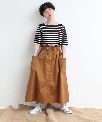 大きなポケットがサイドにあしらわれた、ちょっぴり変わったデザインのブラウンスカート。ボーダートップスをタックインして、女性らしさとカジュアルさを合わせ持つ着こなしに。白のスニーカーがカジュアルさを後押ししてくれているので、バッグや小物は茶系や黒で大人っぽくまとめると良さそう。