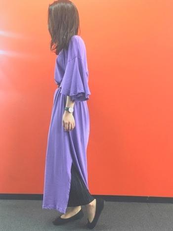 サイドスリット入りのパープルカラーのロングワンピースに黒いスカートをレイヤードすることで、シックな大人ムードを高めたスタイリング。長めのフレア袖が、落ち着いた中に可憐な華やかさを添えています。