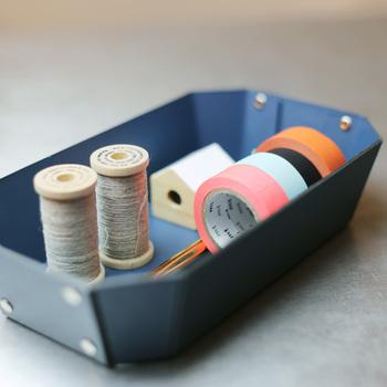 木材繊維(古紙やフレッシュパルプなど)を使用した繊維ボード「パスコ」という素材で作られたトレー。  シンプルなながらも、トレーの内側部分には綺麗に仕上がるよう、両面リベット加工が施されるなどのディテールにこだわったアイテム。マットな色合いに、職人の手作業によりひとつひとつ丁寧に打ち込まれたシルバー色のリベットが、デザインのアクセントにもなり、さりげないカッコよさが光ります。