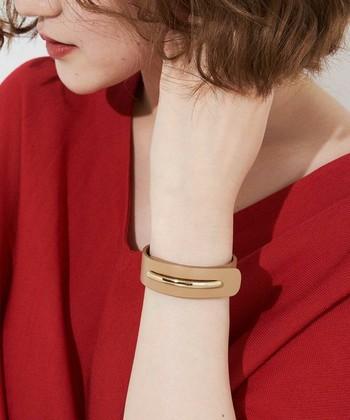 幅が広めのシンプルなレザーブレスレットは、ゴールドアクセとの相性が良いですよ。ブレスレットを留める役目も兼ねているゴールドパーツがきれいめな印象です。