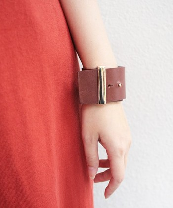 時計のようなデザインのレザーブレスレット。幅広のブレスレットは、腕を細く見せてくれます。肌なじみのよいブラウンカラーも大人っぽくて素敵。