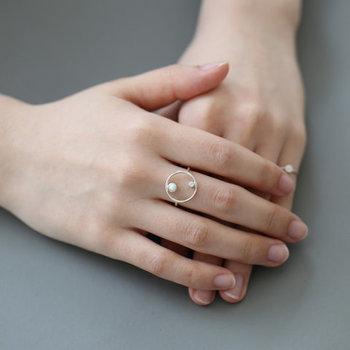 丸い形と小さな石が特徴のリング。個性的な形ながらも、細身なのでシンプルで大人っぽい印象です。丸い石がついたリングと組み合わせると統一感が出ますよ。
