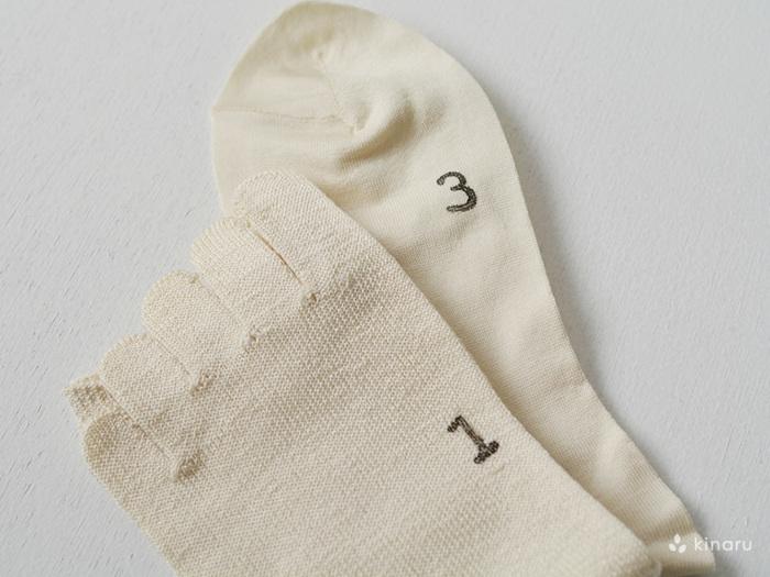 「冷えとり靴下」は5本指のソックス2枚と、先丸ソックス2枚がセットになっています。写真のように「履き順スタンプ」が押されているので、順番を迷うことなく、スムーズに履くことができますよ。また、4足重ねても違和感なく快適に履けるよう、それぞれの靴下の長さや生地の厚みを変えるという、独自の工夫も施されています。デザインにも素材にもとことんこだわって作られた「冷えとり靴下」は、コーディネートに馴染むシンプルさと、天然素材ならではの優しい肌触りも魅力です。
