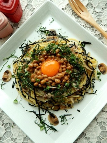 """すりおろしニンニクと""""白だし""""で具材を炒める、風味豊かな納豆パスタ。卵黄を乗せるパスタは、すべて全体をよく混ぜていただくのがポイント!"""