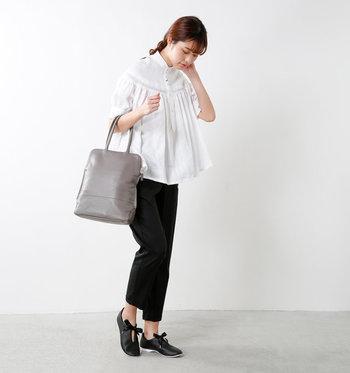 白のシャツブラウス×黒パンツのモノトーンコーデに、中間色のライトグレーのスクエアバッグを取り入れたスタイリング。足元はリボンシューレースのレザースリッポンで、大人の可愛らしさを添えて。