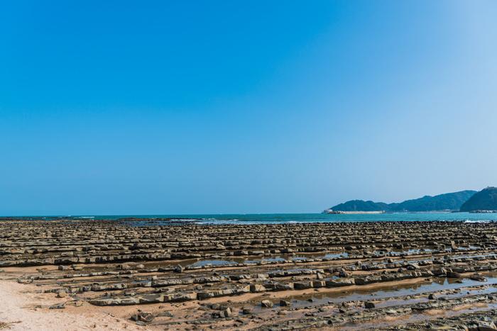 青島の周りは「鬼の洗濯板」と呼ばれる奇岩に囲まれています。約700万年前の中新世後期に、海中の水成岩が隆起し、長い時間の経過で波に削られ板が重なったようになりました。一度は見てみたい、島と海の間に広がる不思議な光景です。