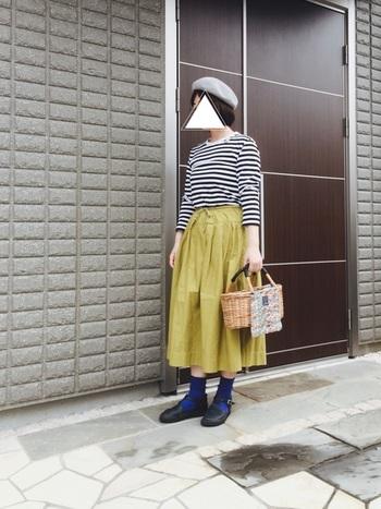 モノトーンボーダー×マスタードイエローのスカートスタイルに、黒のオーロラシューズを合わせたスタイリング。ブルーのソックスで、秋コーデにほんのり個性を添えて。